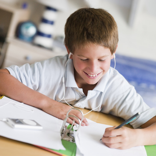 """""""Boy doing homework while listening to music"""" stock image"""