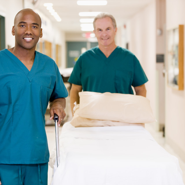 """""""Two Orderlies Pushing An Empty Bed Down A Hospital Corridor"""" stock image"""