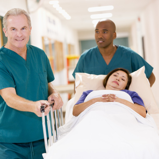 """""""Two Orderlies Pushing A Woman In A Bed Down A Hospital Corridor"""" stock image"""