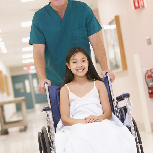 """""""An Orderly Pushing A Little Girl In A Wheelchair Down A Hospital Corridor"""" stock image"""