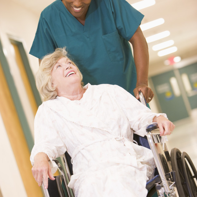 """An Orderly Pushing A Senior Woman In A Wheelchair Down A Hospital Corridor"" stock image"