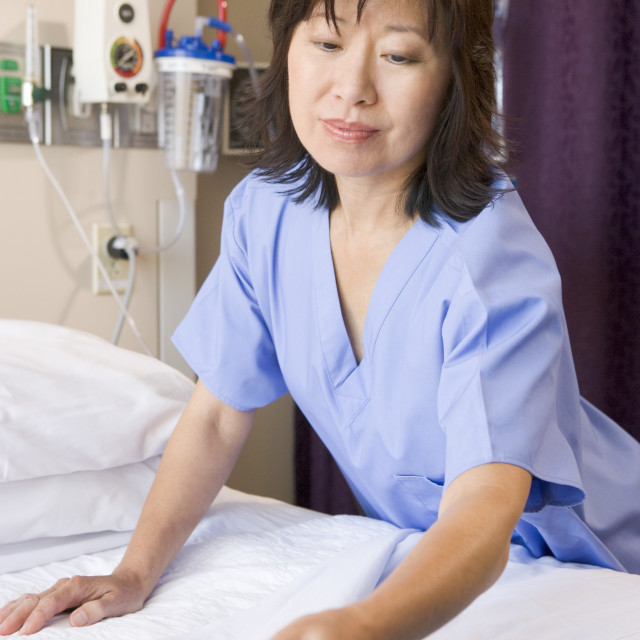 """A Nurse Making A Bed In A Hospital Ward"" stock image"