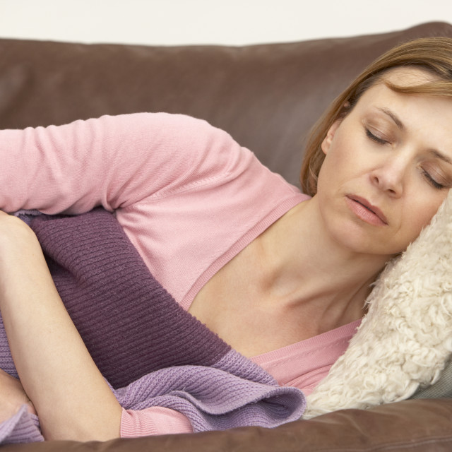 """Woman Unwell And Lying On Sofa"" stock image"