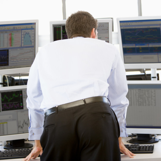 """Stock Trader Looking At Multiple Monitors"" stock image"
