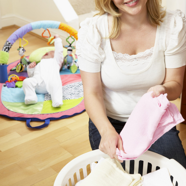 """""""Mother Folding Baby Clothes At Home"""" stock image"""
