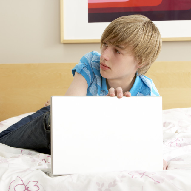 """Guilty Teenage Boy Using Laptop In Bedroom"" stock image"