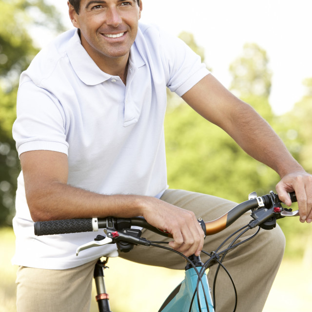 """""""Young man riding bike in countryside"""" stock image"""