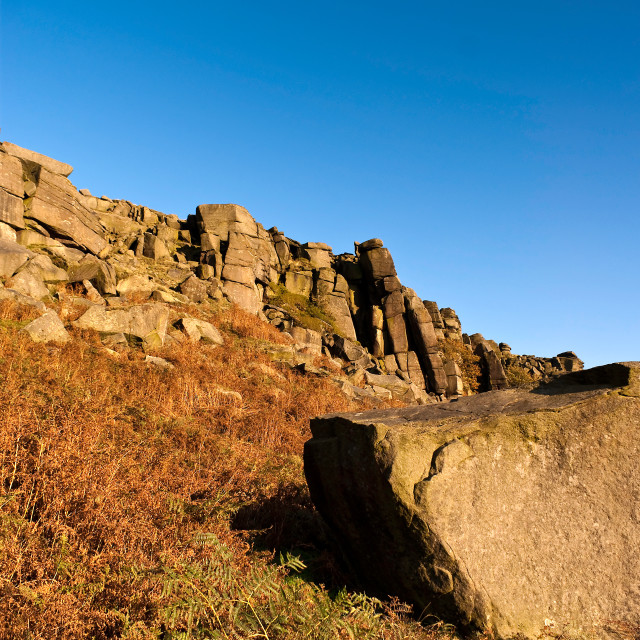 """A rocky outcrop against a clear blue sky"" stock image"