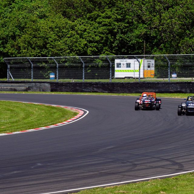 """Two Caterham 7 Sports cars taking a bend at Castle Combe"" stock image"