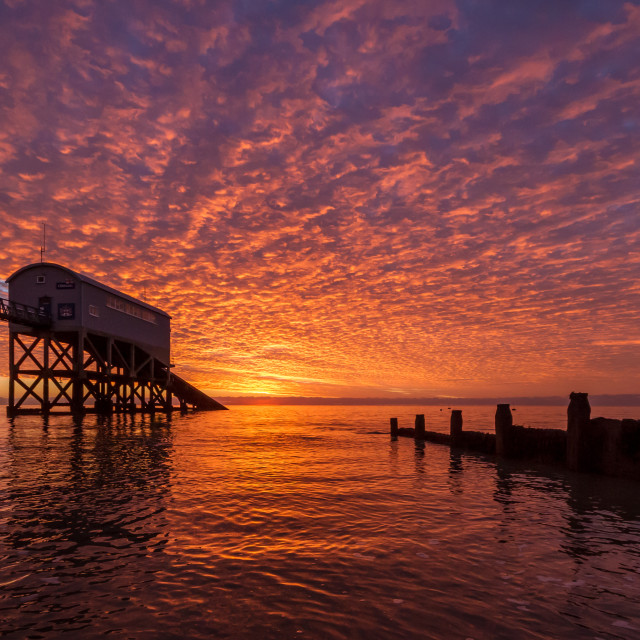 """Sunrise reflecting on the clouds at Selsey Beach"" stock image"
