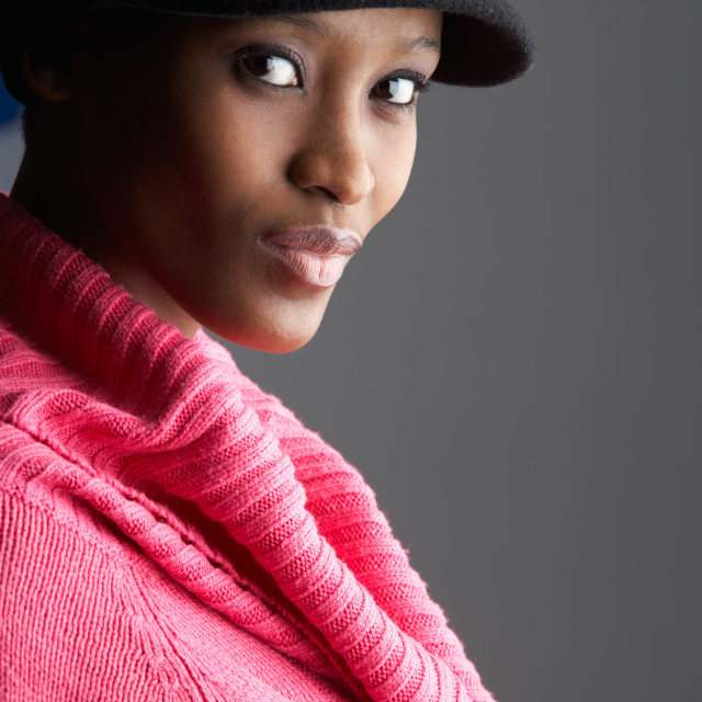"""Fashionable Young Woman Wearing Cap And Knitwear In Studio"" stock image"