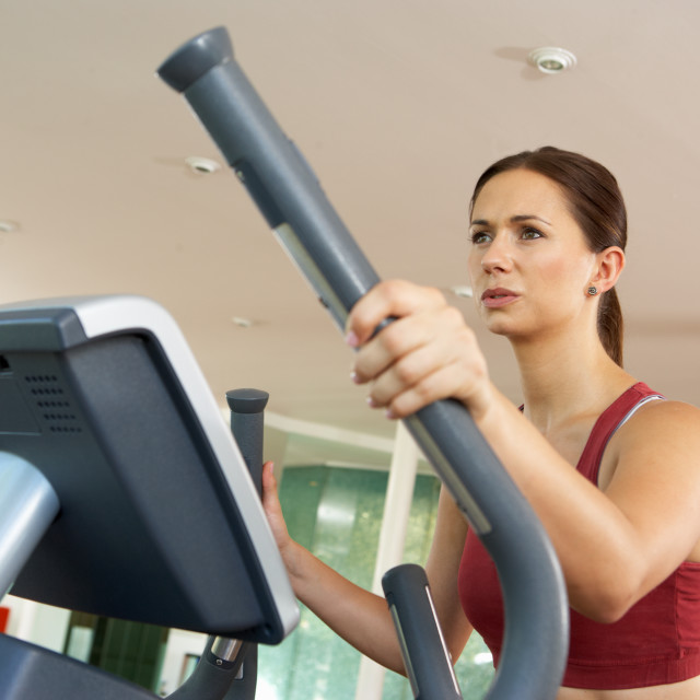 """""""Woman On Cross Trainer Machine In Gym"""" stock image"""