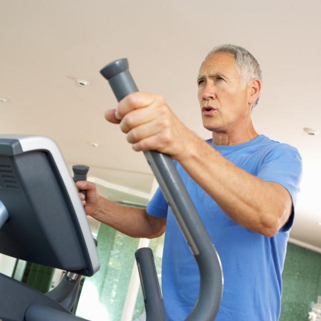 """Senior Man On Cross Trainer In Gym"" stock image"