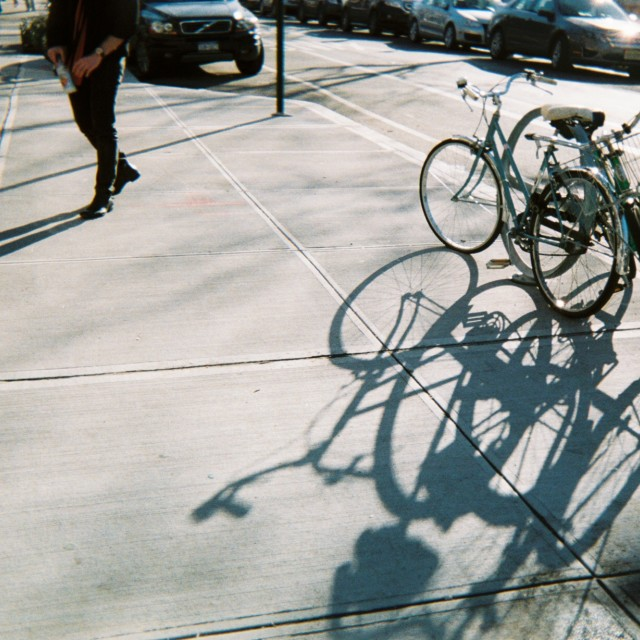 """Bikes on a Sidewalk Shadows"" stock image"