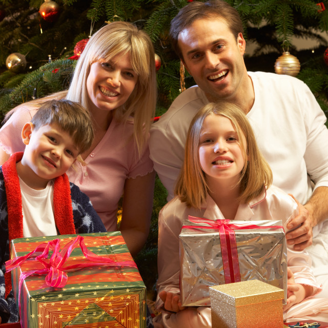"""""""Family Opening Christmas Present In Front Of Tree"""" stock image"""