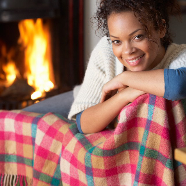 """Young woman sitting by open fire"" stock image"