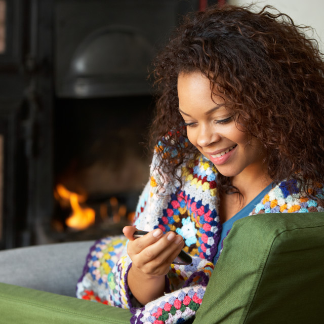 """Young woman sitting by fire with phone"" stock image"