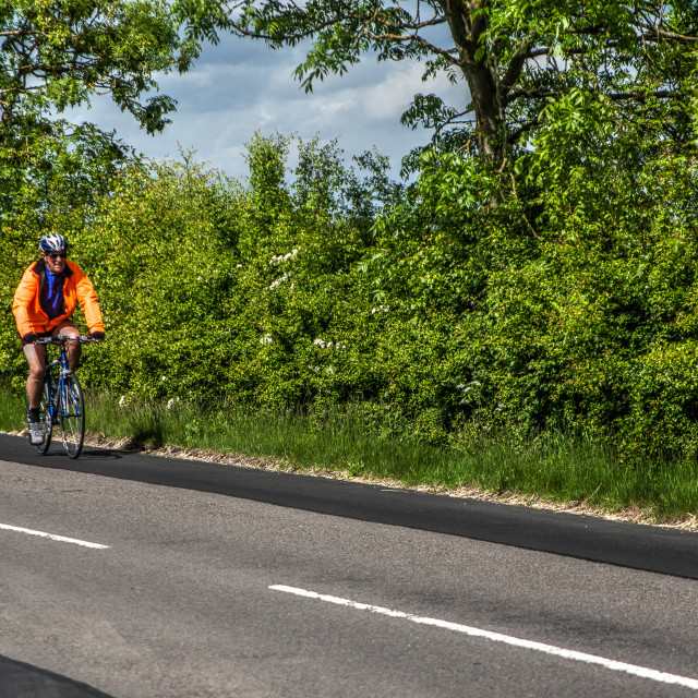 """Man cycling along country roads"" stock image"