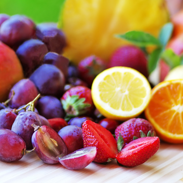 """""""Assortment of fruits on wooden table on green background"""" stock image"""