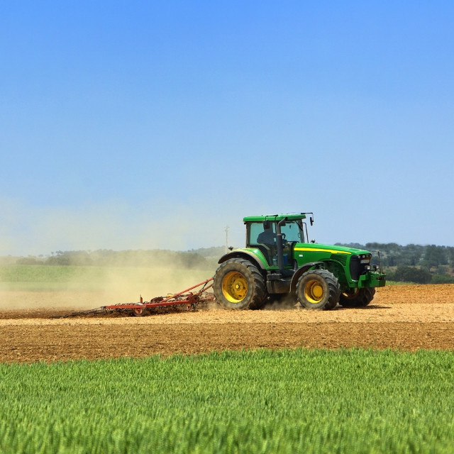 """""""Green tractor working in the field."""" stock image"""