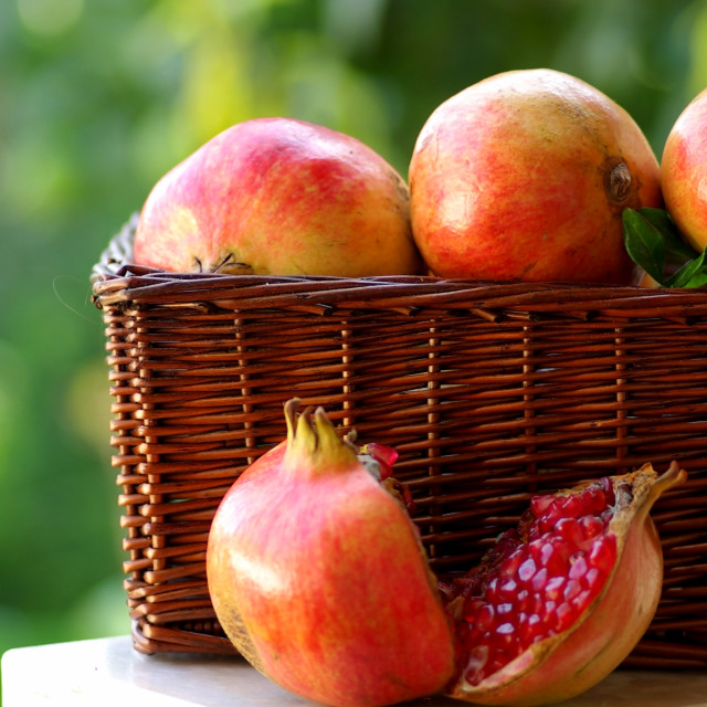 """basket with red fruits of the Autumn:Pomegranates"" stock image"