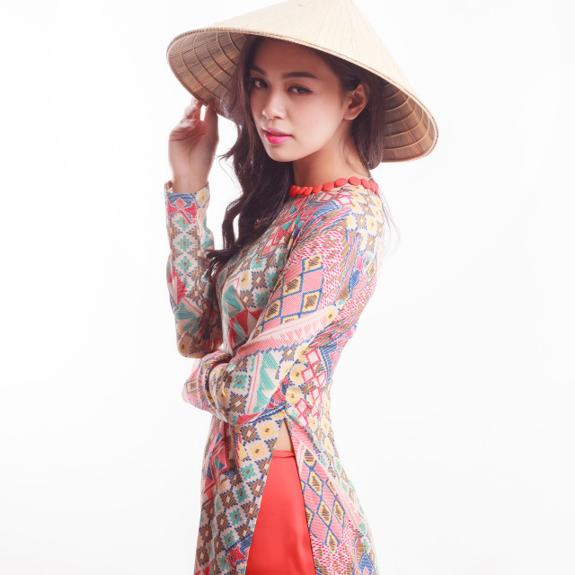 """Beautiful Vietnamese young woman with modern style ao dai and palm-leaf conical hat ( non la ) on white background"" stock image"