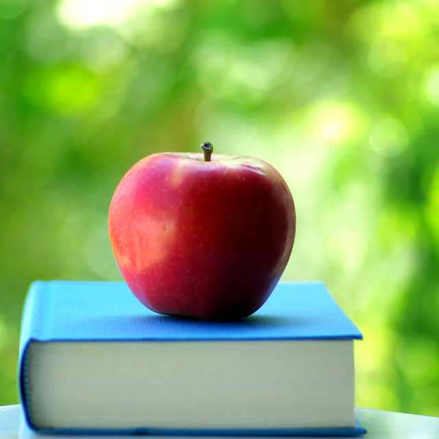 """red apple on a book of blue color"" stock image"