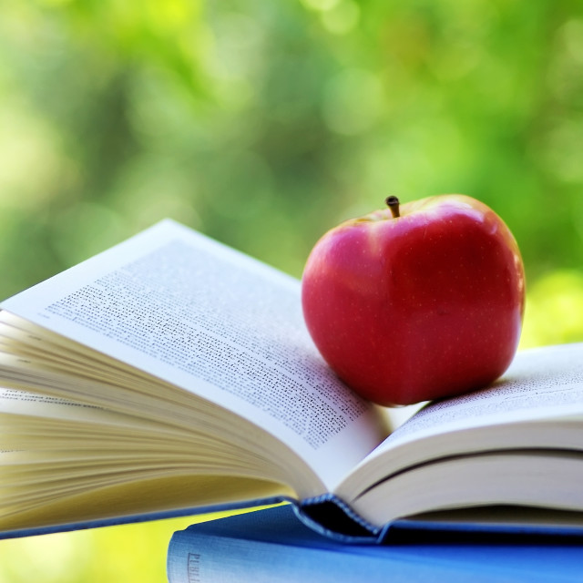 """A red apple on a book"" stock image"