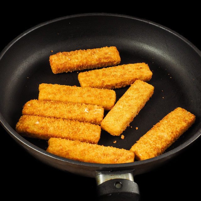 """Crumbed fish fingers in fry pan, isolated on black"" stock image"