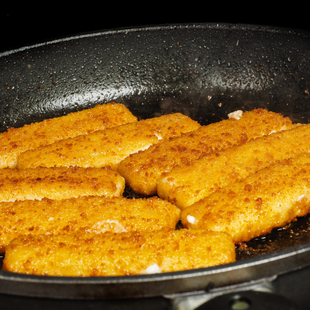 """Closeup of crispy breaded fish fingers in hot fry pan"" stock image"