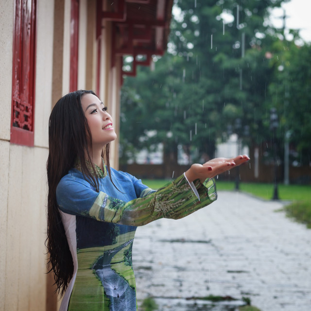 """Vietnamese women wear Ao dai holding umbrella in the rain. Ao dai is famous traditional custume for woman in VIetnam."" stock image"