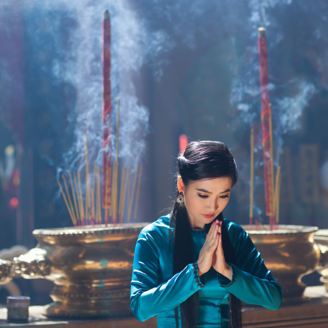 """Vietnamese women wearing Ao dai praying in pagoda"" stock image"