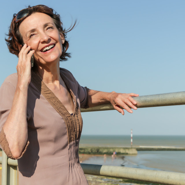 """""""Mature Woman talking on the Beach"""" stock image"""