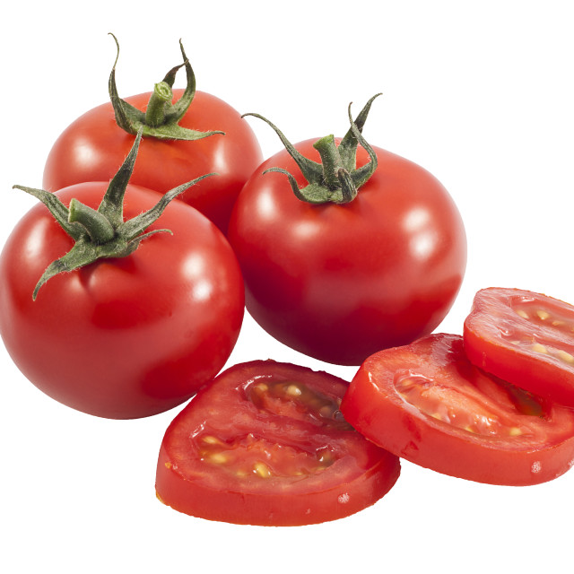 """Three whole tomatoes and one sliced."" stock image"