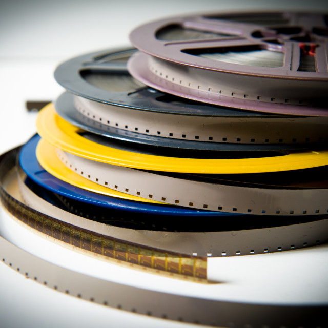 """Pile of 8mm super8 movie reels with color effect and out of focus background"" stock image"