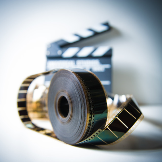 """35mm movie reel with out of focus clapper in background"" stock image"