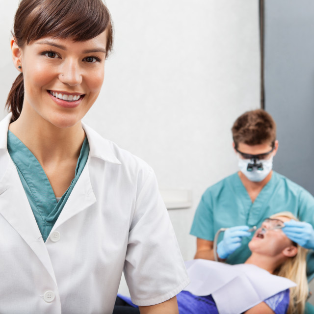 """""""Assistant with dentistry work in the background"""" stock image"""