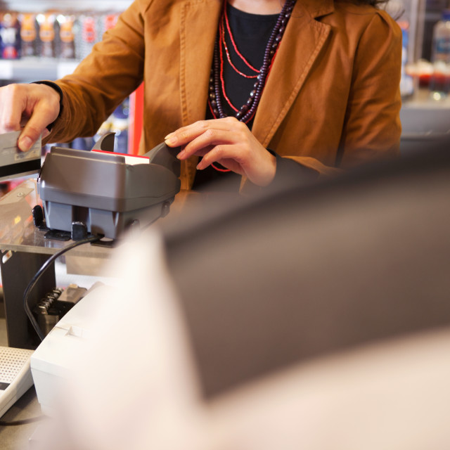 """""""Shop assistant swiping credit card"""" stock image"""