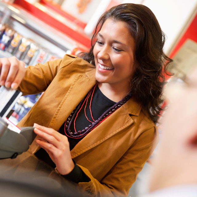 """""""Shop assistant smiling while swiping credit card in supermarket"""" stock image"""