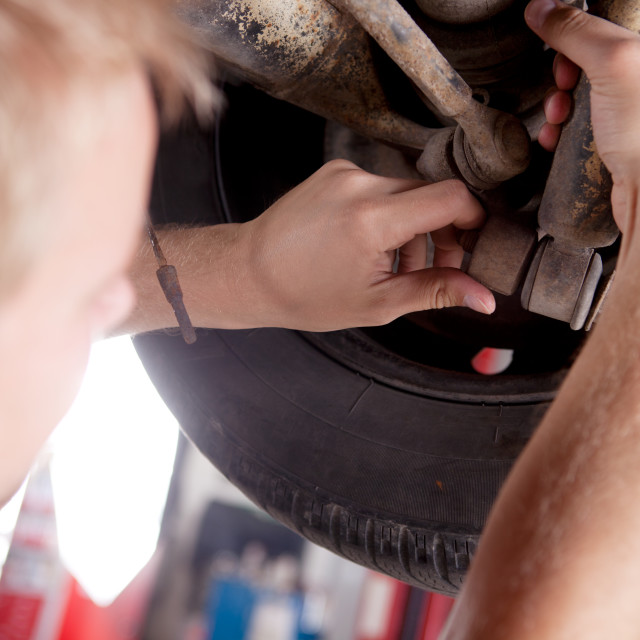 """Mechanic Inspecting Shock Absorber"" stock image"