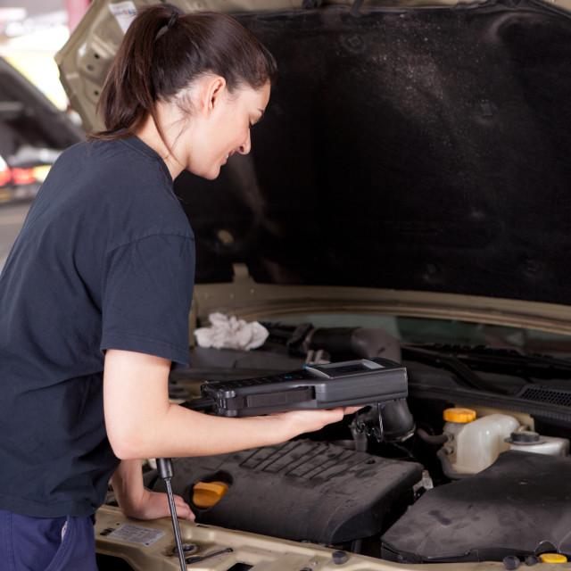 """Woman Mechanic with Engine Diagnostics Tool"" stock image"