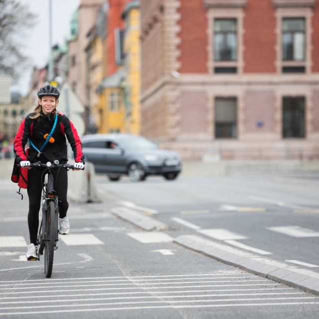 """Female Cyclist With Courier Delivery Bag On Street"" stock image"