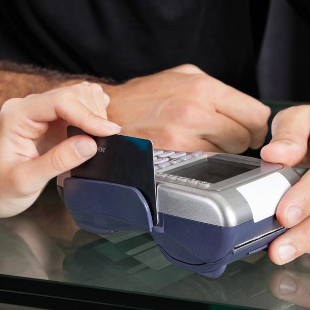 """Hand Swiping Credit Card Through Terminal At Salon"" stock image"
