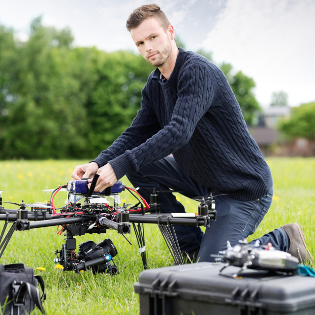 """""""Young Technician Assembling UAV in Park"""" stock image"""
