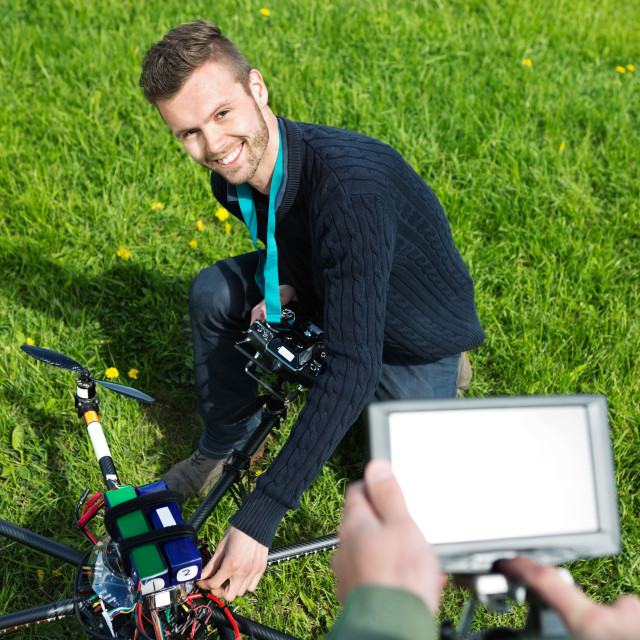 """""""Engineer Fixing UAV Helicopter in Park"""" stock image"""