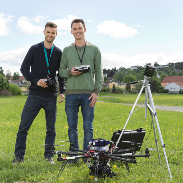"""Engineers Standing By UAV Helicopter And Tripod"" stock image"