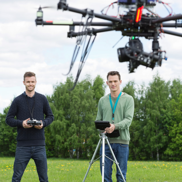 """""""Technicians Flying UAV Helicopter in Park"""" stock image"""
