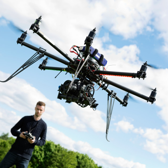 """Technician Flying UAV Helicopter in Park"" stock image"