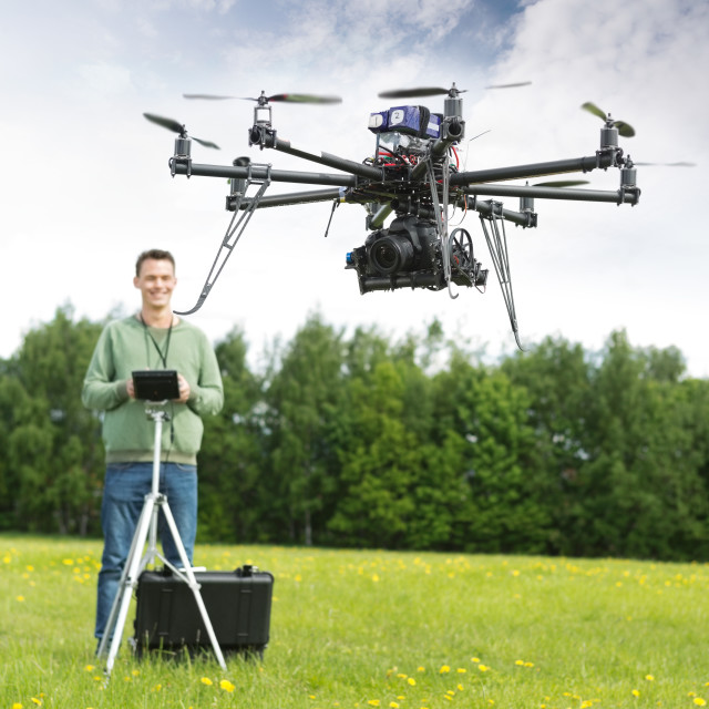 """Man Flying UAV Helicopter in Park"" stock image"