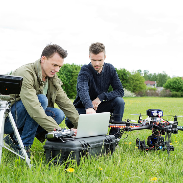 """Technicians Using Laptop By Tripod And UAV"" stock image"